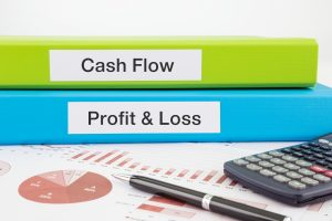 Cash Flow, Profit & Loss words on labels with document binders, graphs and business reports